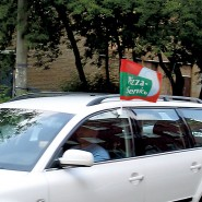 Car, hand waving and window flags
